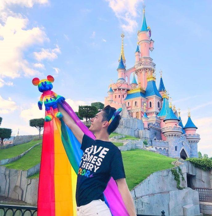 Magical Pride en Disneylandia; chico frente al castillo Disney sosteniendo una bandera de colores y un muñeco de Mickey Mouse