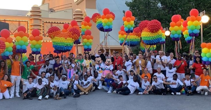 Magical Pride en Disneylandia; gente con Mickey y Minnie Mouse, con globos en forma del ratón de colores del arcoiris
