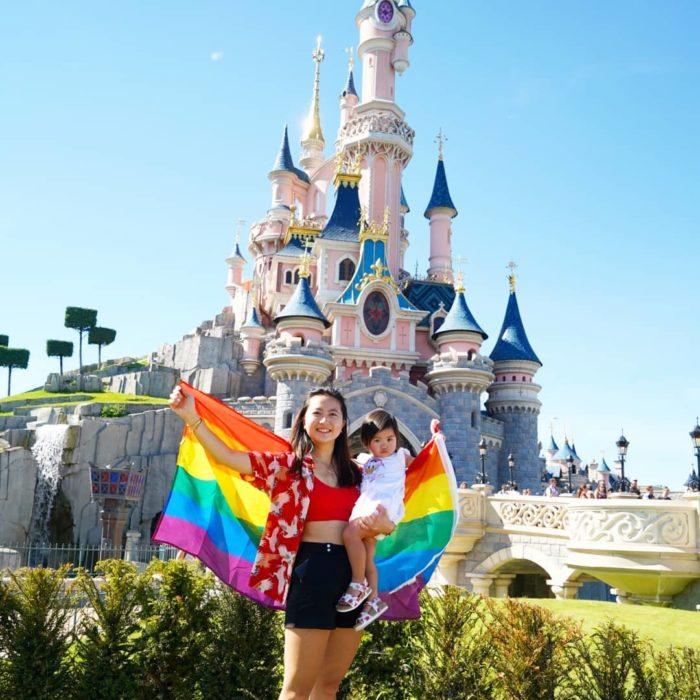 Magical Pride en Disneylandia; mujer y su hija sosteniendo bandera de colores frente a castillo