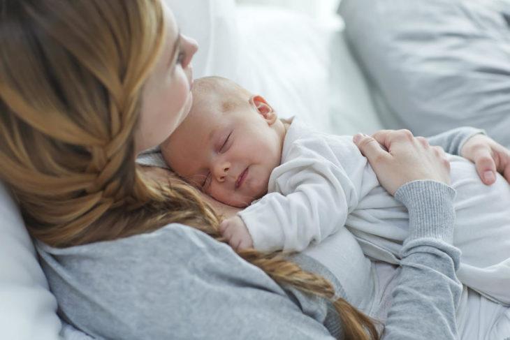 una mamá con su bebé en brazos durmiendo y sonríe
