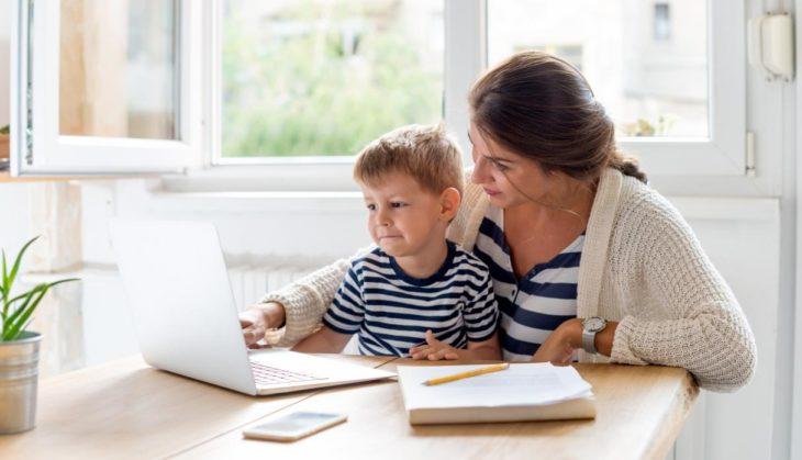 una mamá le muestra algo a su hijo en un ordenador portátil