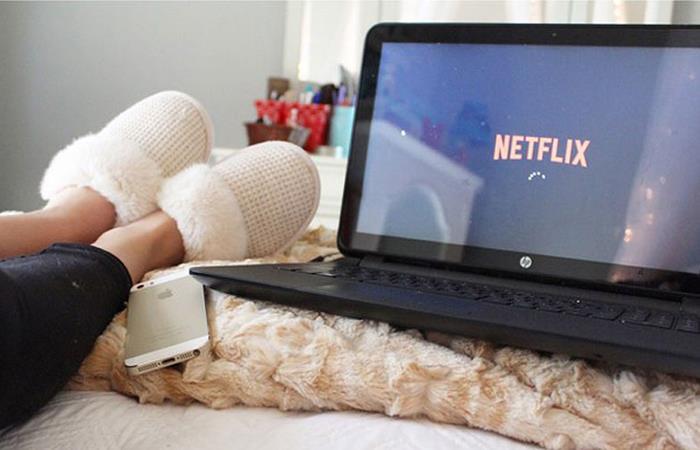 Chica recostada, usando pantuflas, mirando Netflix