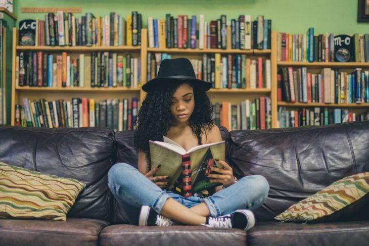 Chica sentada en un sofá leyendo un libro