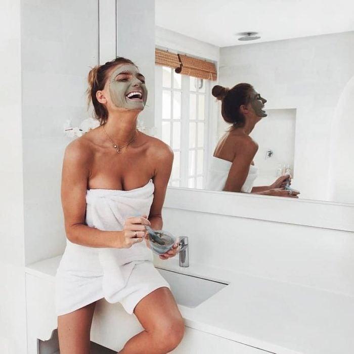 Chica con una toalla enredada, sobre un lavabo, aplicando una mascarilla verde