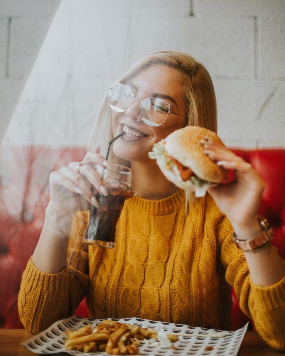 Chica bebiendo soda y sosteniendo una hamburguesa dentro de un restaurante