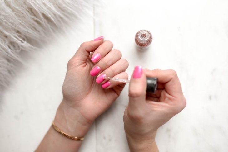 Chica pintando sus uñas con esmalte rosa