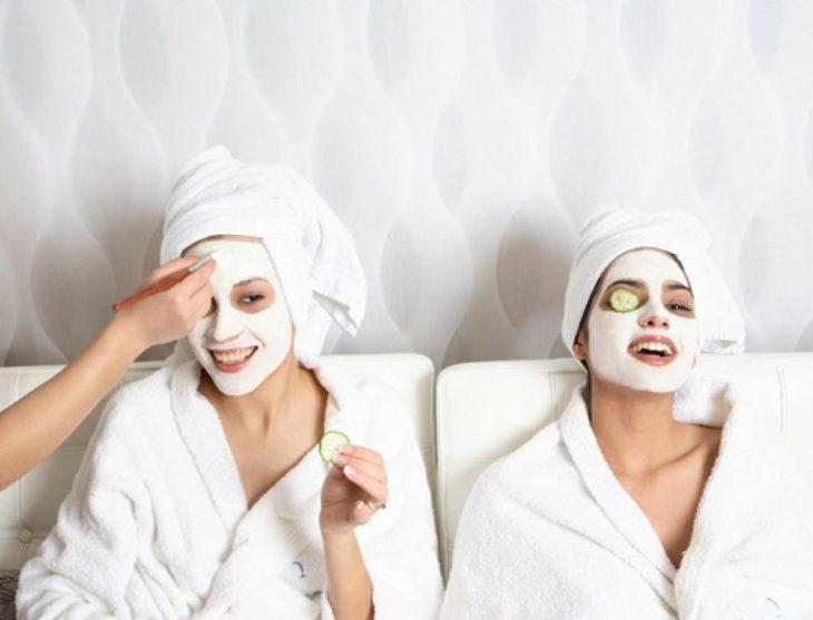 Par de mujeres dentro de un spa con mascarillas y pepinos en el rostro