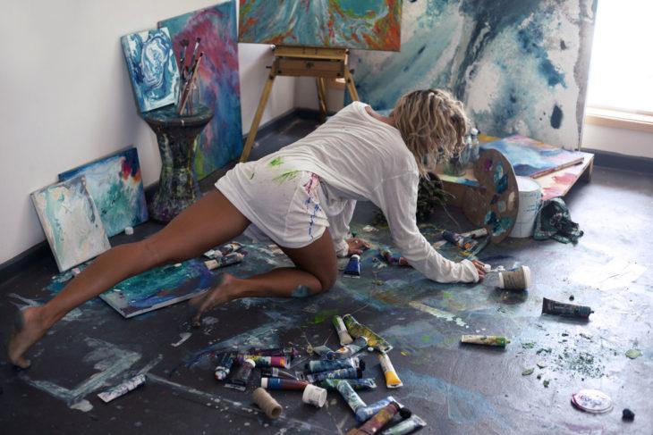 Chica sobre un piso de madera lleno de pintura de oleo, pintando