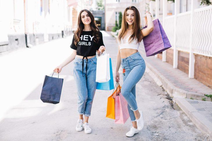 Amigas de compras sosteniendo bolsas de papel de colores en medio de la calle