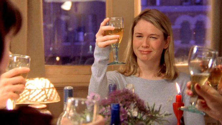 Escena de el diario de bridget Jones. Bridget brindando con una copa en una reunión familiar