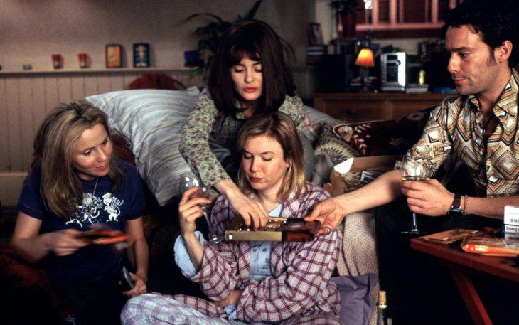Escena del Diario de Bridget Jones. Peronaje sentado a la orilla de la cama comiendo chocolates con sus amigos