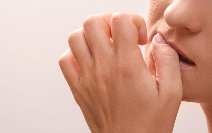 una mujer se muerde la uña del dedo gordo de la mano izquierda no se le ve la cara completa