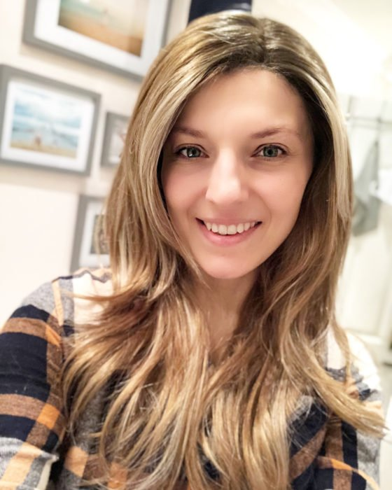 Michelle Wilson Stimson usando una peluca y sonriendo mientras oculta su alopecia