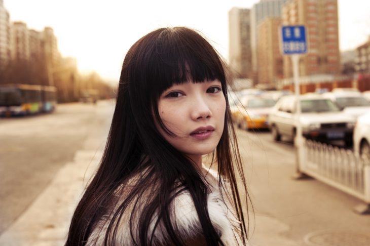 China da vacaciones para mujeres solteras; mujer oriental de cabello largo, lacio y suelto, con fleco
