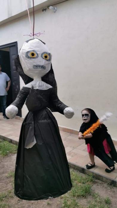 Niña disfrazada de monja quebrando una piñata del personaje de La Monja