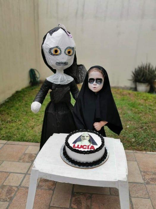 Niña frente a un pastel de cumpleaños, en un jardín, disfrazada de La Monja