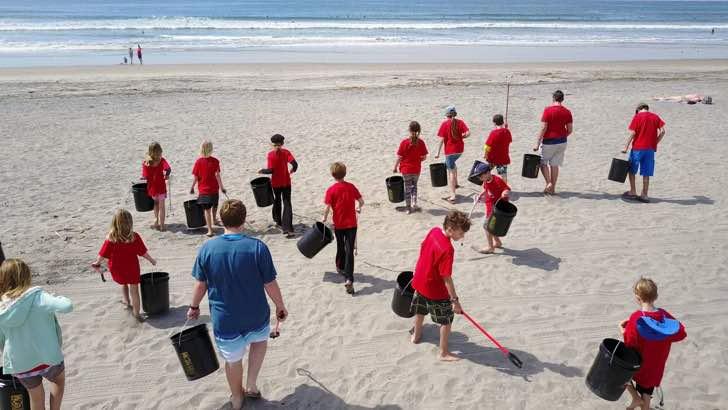 Niños limpiando una playa de manera exhaustiva para que no contamine el mar