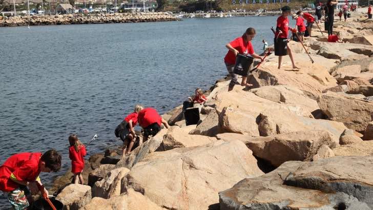 Niños sobre las rocas limpiando las playas de la basura y la contaminación