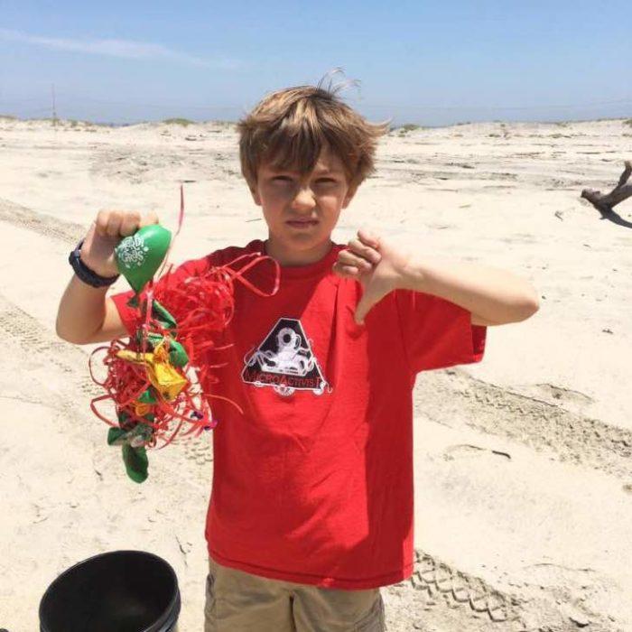 Niño sosteniendo basura en sus manos luego de limpiar una playa