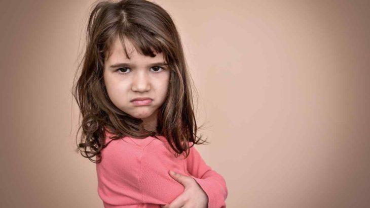 una niña de pelo castaño hasta los hombros y con brazos cruzados mira a la cámara con aspecto enojado