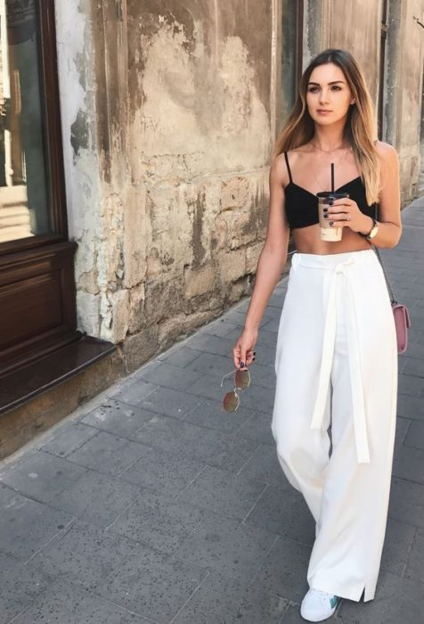 Chica usando pantalones ampones, bebiendo agua de sabor