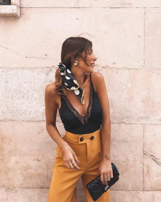 Chica recargada en la pared, posando de perfil, con pañoleta en el cabello