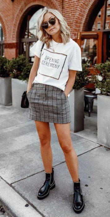 Chica modelando una falda a cuadros en medio de la avenida