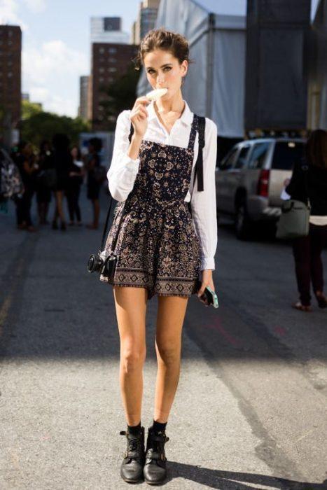 chica usando un jumpsuit, comiendo helado a mitad de avenida