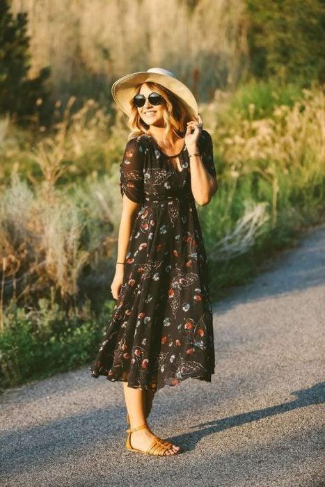 Chica en el campo usando vestido con flores y sombrero