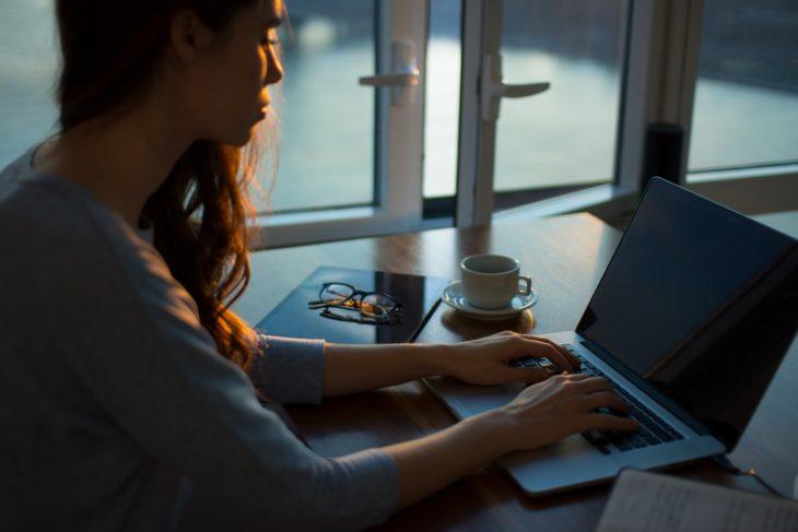 mujer sentada en escritorio frente a laptop