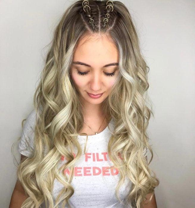 Peinados para el calor; chica de cabello rubio, largo y ondulado, con dos trenzas adornadas con anillos en la parte de arriba