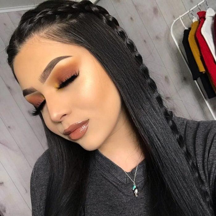 Peinados para el calor; chica con los ojos cerrados, sombras café, anaranjada y amarilla, y cabello negro y lacio peinado con una trenza de lado