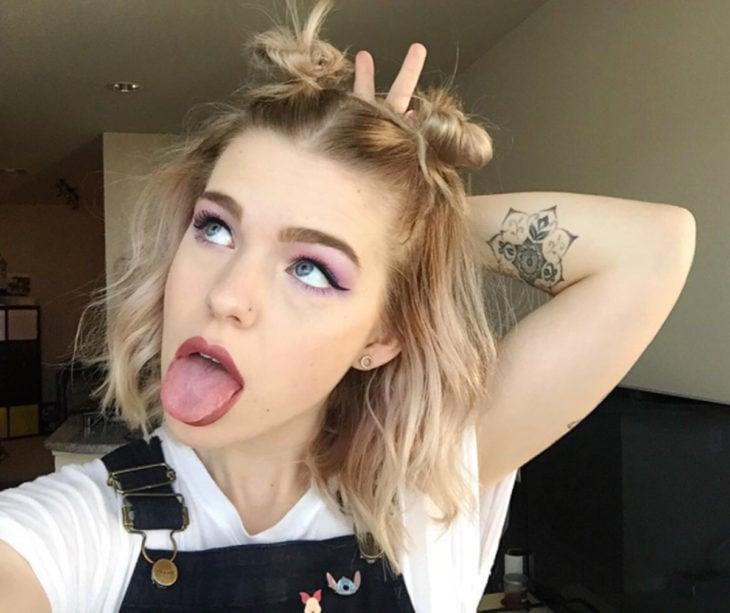Peinados para el calor; muchacha haciendo cara chistosa con lengua de fuera, cabello rubio y corto con dos chonguitos altos