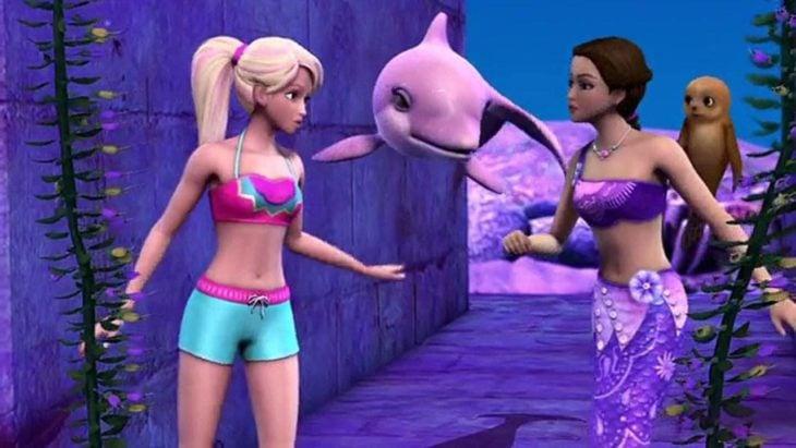 Escena de la película Barbie en una aventura de sirenas. Barbie junto a un delfín y su amiga nadando