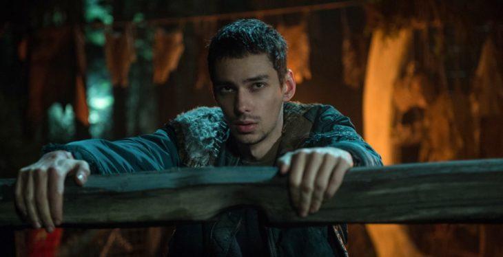 Jasper Jordan detrás de una cerca de madera, escena de la serie The 100