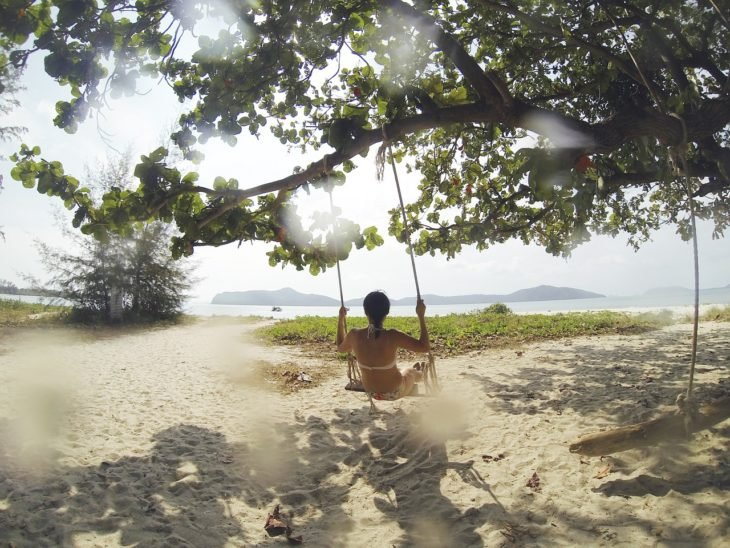 una chica se pasea en un columpio que pende de un árbol frente a la playa