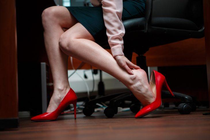 Mujer en oficina con zapatos de tacón rojo