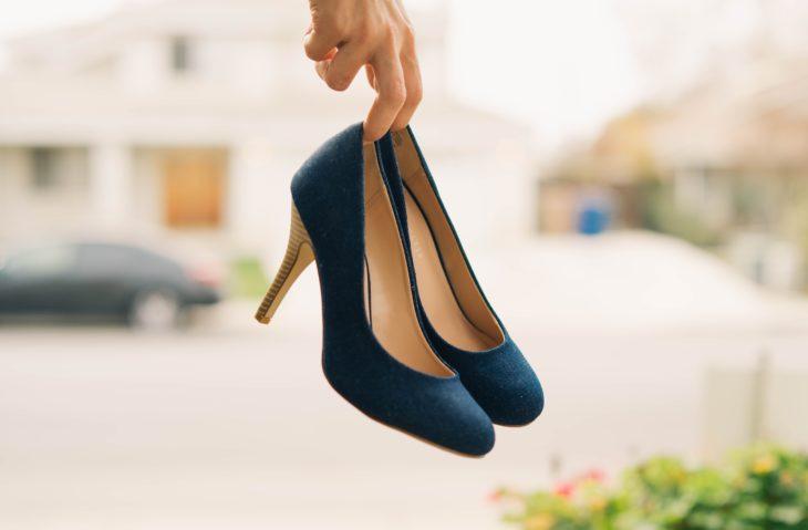 mujer con zapatos de tacón en una mano
