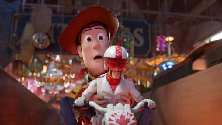 Escena de la película Toy Story 4. Woody sujetando a Duke Caboom mientras van en una motocicleta