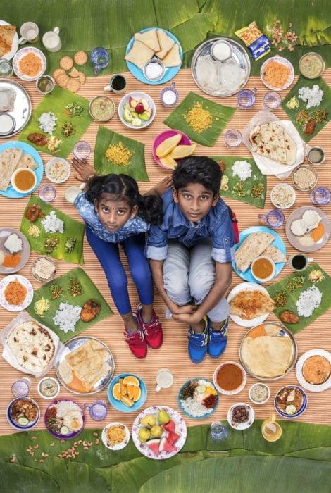 Par de hermanos sentados sobre una alfombra melón, rodeados de comida, royecto fotográfico de Gregg Segal