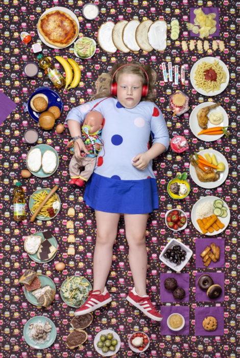 Niña recostada en una alfombra morada, rodeada de comida, proyecto fotográfico de Gregg Segal