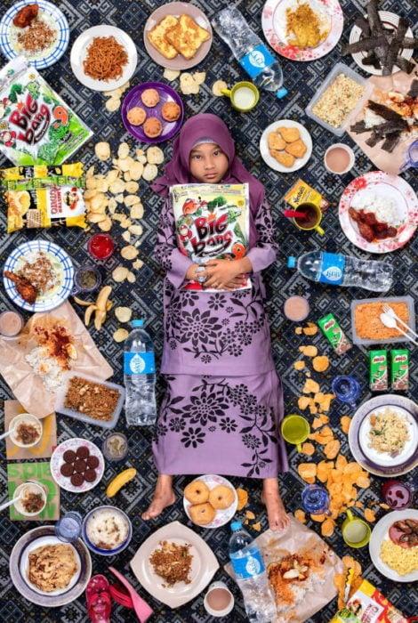 Niña con turbante recostada en el piso, rodeada de alimentos, proyecto fotográfico de Gregg Segal