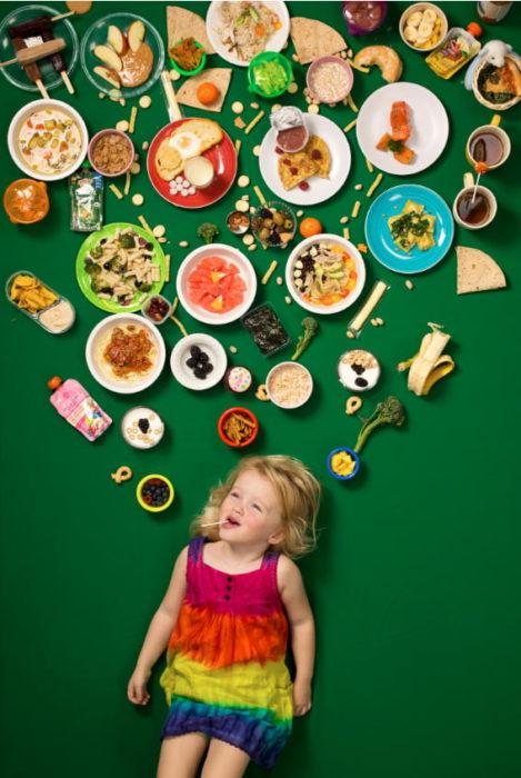 Niña recostada en una alfo,bra verde, rodeada de comida, proyecto fotográfico de Gregg Segal