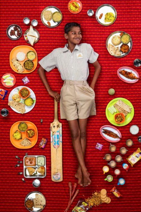 Niño con short color beige, recostado sobre una alfombra roja, proyecto fotográfico de Gregg Segal