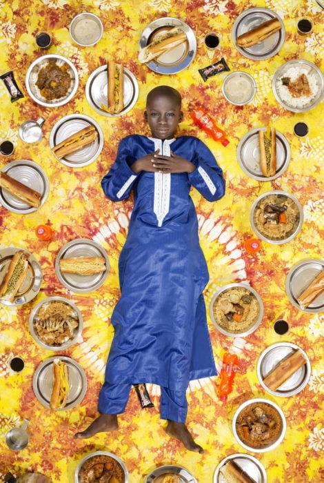 niño con ropa azul marino, recostado en el piso, rodeado de comida, proyecto fotográfico de Gregg Segal