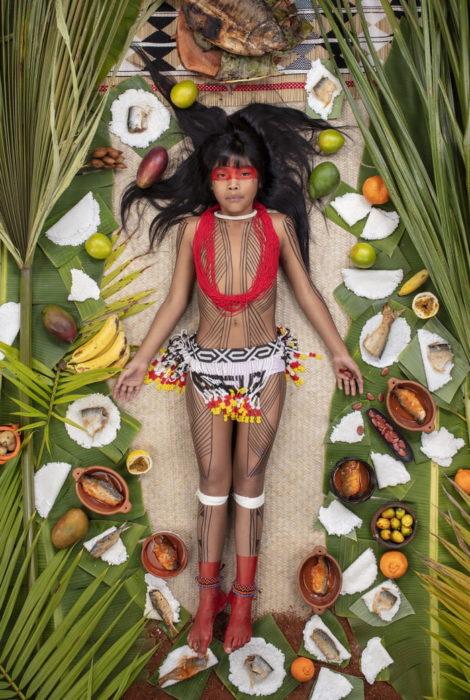 Niña con maquillaje en el rostro, recostada en el piso, rodeada de comida, proyecto fotográfico de Gregg Segal