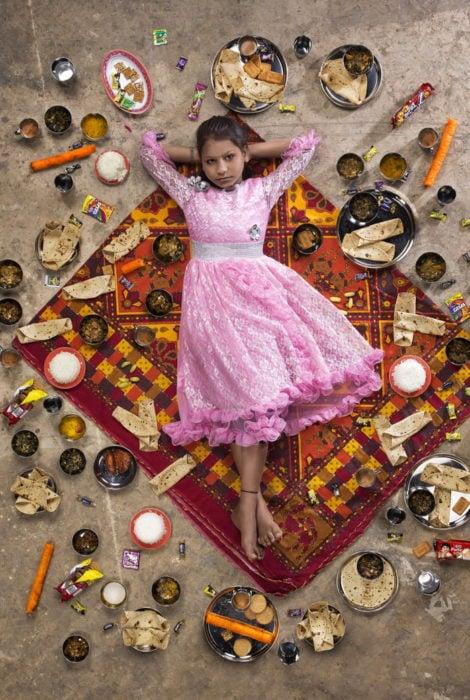 Niña con vestido rosado, recostada sobre una alfombra roja, rodeada de comida, proyecto fotográfico de Gregg Segal