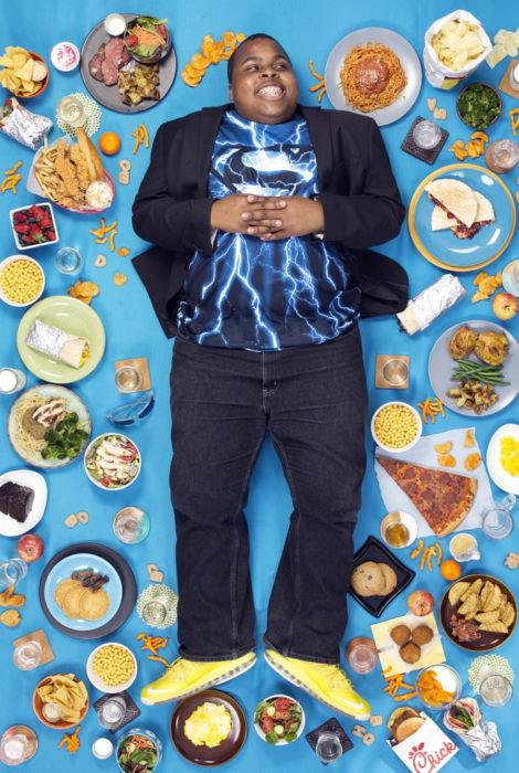 Niño con traje sastre en tono azul marino, recostado sobre una tela azul cielo, rodeado de comida, proyecto fotográfico de Gregg Segal