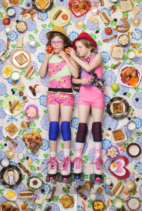 Hermanas recostadas en el piso, rodeadas de comida frutal, proyecto fotográfico de Gregg Segal