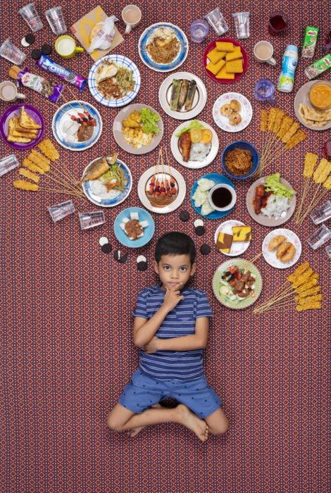 Chico recostado en el piso, rodeado de comida sobre su cabeza, proyecto fotográfico de Gregg Segal
